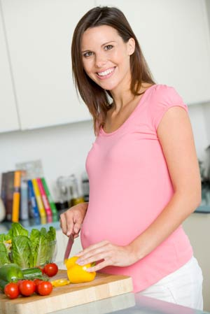 Pregnant woman slicing vegetables