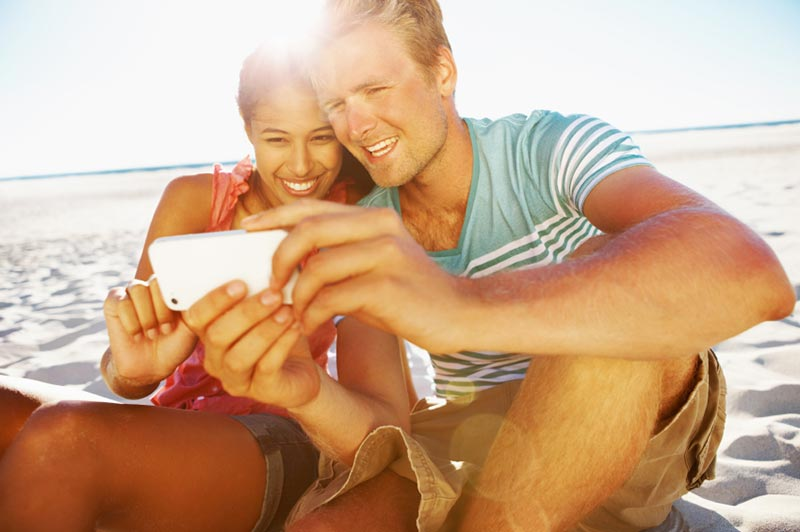 Couple on beach with cellphone